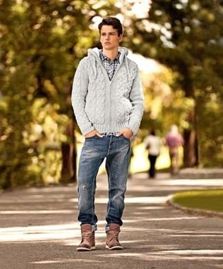 Cómo combinar: sudadera con capucha de punto gris, camisa de manga larga a cuadros en blanco y azul marino, vaqueros desgastados azul marino, botas casual de cuero marrónes