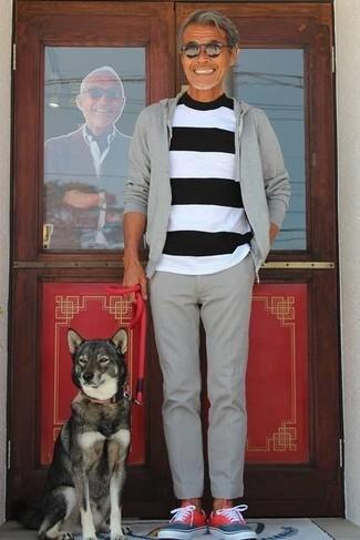 Cómo combinar: sudadera con capucha gris, camiseta con cuello circular de rayas horizontales en blanco y negro, pantalón de vestir de lana gris, tenis rojos