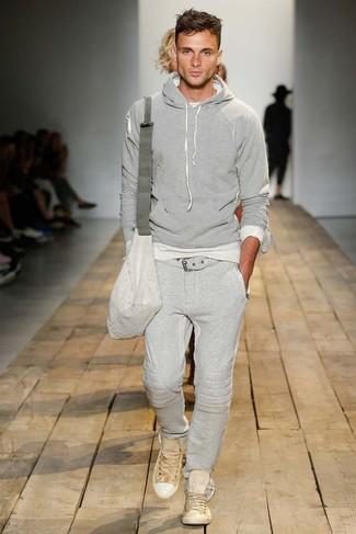 Cómo combinar: sudadera con capucha gris, pantalón de chándal gris, tenis marrón claro, bolso mensajero de lona gris