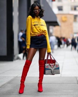 Cómo combinar: sudadera con capucha estampada amarilla, minifalda vaquera azul marino, botas sobre la rodilla de ante rojas, mochila con cordón de ante roja