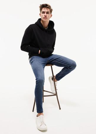 Cómo combinar: sudadera con capucha negra, vaqueros pitillo azules, tenis de cuero blancos