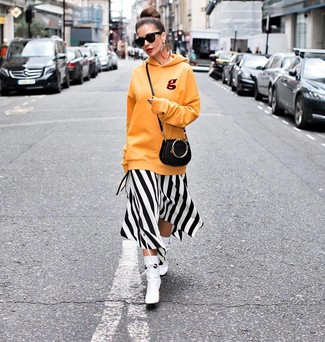 Cómo combinar: sudadera con capucha naranja, vestido midi de rayas verticales en blanco y negro, botines de cuero blancos, bolso bandolera de cuero negro