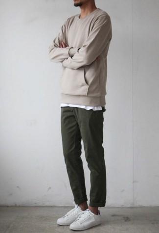 Cómo combinar un pantalón chino verde oscuro: Para crear una apariencia para un almuerzo con amigos en el fin de semana elige una sudadera en beige y un pantalón chino verde oscuro. Este atuendo se complementa perfectamente con tenis de cuero blancos.