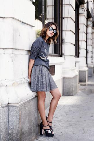 Cómo combinar: sudadera estampada en gris oscuro, falda skater gris, sandalias de tacón de ante bordadas negras, gafas de sol plateadas