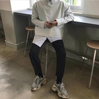 Cómo combinar: sudadera gris, camisa de manga larga blanca, pantalón chino negro, deportivas grises