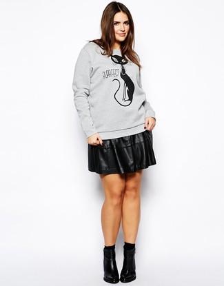 Cómo combinar: sudadera estampada gris, falda skater de cuero negra, botines de cuero negros, calcetines negros