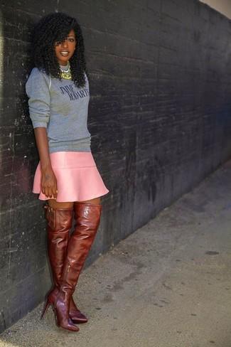 Cómo combinar: sudadera estampada gris, falda skater de cuero rosada, botas sobre la rodilla de cuero marrónes, collar en multicolor
