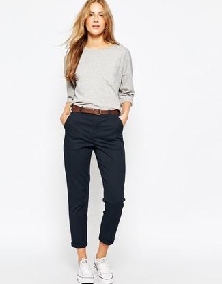 Cómo combinar un pantalón chino negro: Para un atuendo tan cómodo como tu sillón intenta ponerse una sudadera gris y un pantalón chino negro. Tenis de lona blancos son una opción excelente para complementar tu atuendo.