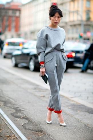 Cómo combinar: sudadera gris, pantalón de vestir de lana gris, zapatos de tacón de cuero plateados, reloj de cuero gris