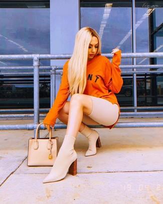 Cómo combinar: sudadera estampada naranja, mallas ciclistas en beige, botines de elástico en beige, bolsa tote de cuero en beige