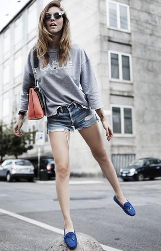 Cómo combinar: sudadera estampada gris, pantalones cortos vaqueros azules, náuticos de lona azul marino, bolso bandolera de cuero rojo
