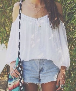 Cómo combinar: top con hombros descubiertos blanco, pantalones cortos vaqueros celestes, bolso bandolera de lona en multicolor, collar dorado