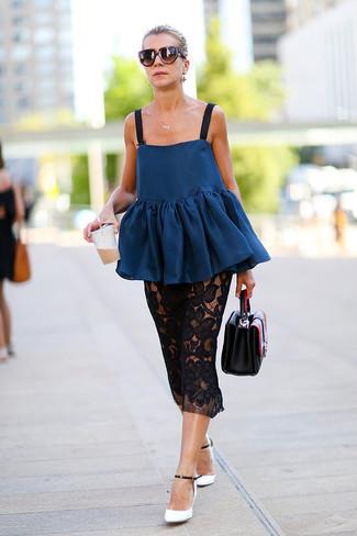 Cómo combinar: top con sobrefalda azul marino, falda midi de encaje negra, zapatos de tacón de cuero en blanco y negro, cartera de cuero negra
