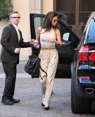 Look de Selena Gomez: Top Corto Blanco, Pantalones Anchos en Beige, Zapatos de Tacón de Ante Negros, Bolso de Hombre de Cuero Negro