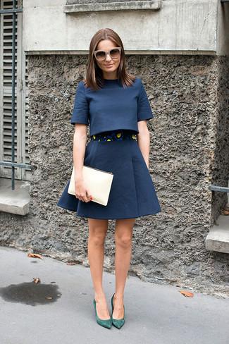Cómo combinar: top corto azul marino, falda campana azul marino, zapatos de tacón de ante verdes, cartera sobre de cuero en beige