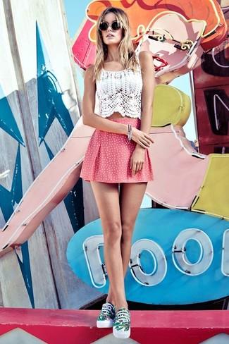 Opta por un top corto de crochet blanco y una falda skater a lunares rosada transmitirán una vibra libre y relajada. Completa el look con tenis en blanco y verde.