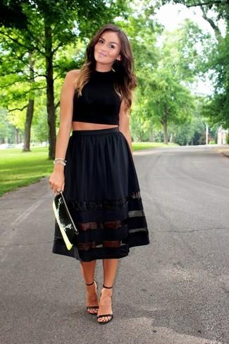 Cómo combinar: top corto negro, falda campana negra, sandalias de tacón de cuero negras, cartera sobre de cuero en negro y blanco