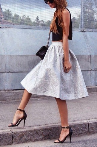 Un top corto negro y una falda campana plateada son prendas que debes tener en tu armario. Luce este conjunto con sandalias de tacón de cuero negras.