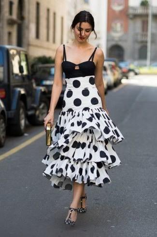 Cómo combinar: top corto negro, falda midi a lunares en blanco y negro, zapatos de tacón de cuero a lunares en negro y blanco, cartera sobre dorada