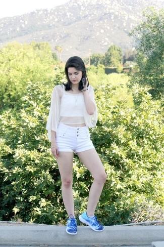 Cómo combinar: top corto de crochet blanco, pantalones cortos blancos, tenis azules, colgante blanco