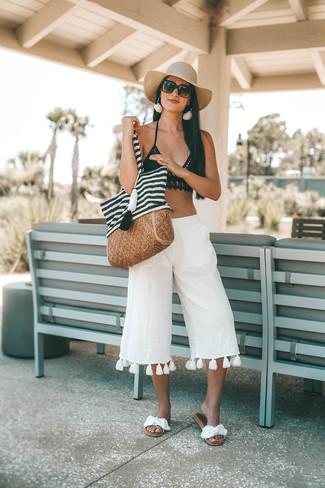 Cómo combinar: top de bikini de crochet negro, falda pantalón de lino blanca, sandalias planas de lona blancas, bolsa tote de lona de rayas horizontales en blanco y negro