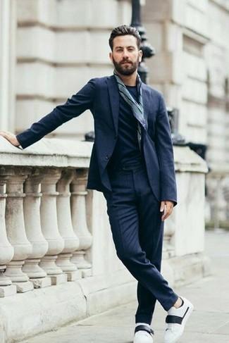 Cómo combinar unos tenis de cuero en blanco y negro: Casa un traje azul marino con una camiseta con cuello circular azul marino para lograr un look de vestir pero no muy formal. Mezcle diferentes estilos con tenis de cuero en blanco y negro.