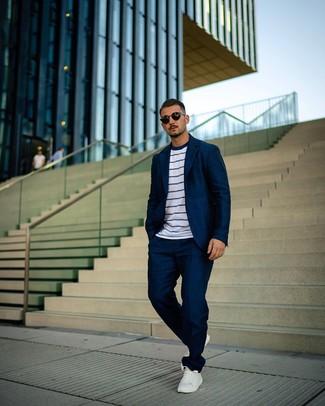 Cómo combinar: traje azul marino, camiseta con cuello circular de rayas horizontales en blanco y azul marino, tenis de cuero blancos, gafas de sol negras