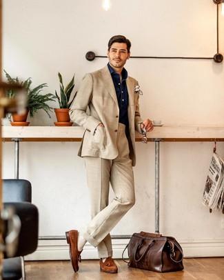 Cómo combinar: traje en beige, camisa de manga larga de cambray azul marino, mocasín con borlas de ante en tabaco, bolsa de viaje de cuero en marrón oscuro