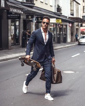 Cómo combinar: traje azul marino, camisa de manga larga blanca, tenis de cuero blancos, bolsa de viaje de cuero estampada en marrón oscuro