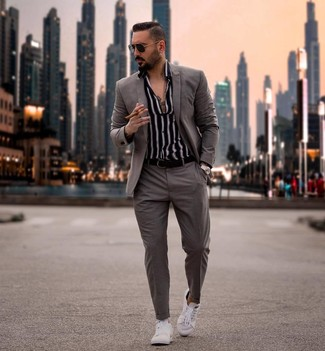 Cómo combinar: traje gris, camisa de manga larga de rayas verticales en negro y blanco, tenis blancos, correa de cuero negra