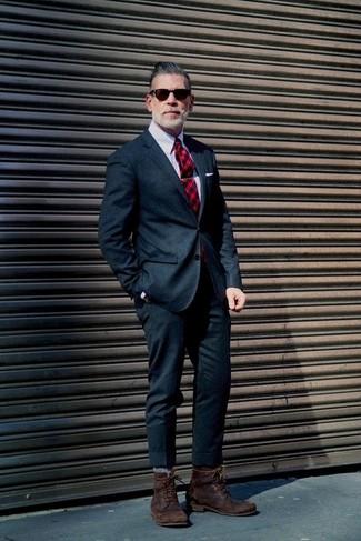 Elige un traje de lana azul marino y una camisa de vestir de rayas verticales gris para una apariencia clásica y elegante. Mezcle diferentes estilos con botas casual de cuero en marrón oscuro.