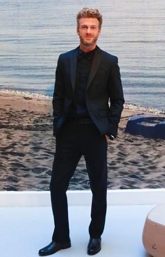 Cómo combinar: traje negro, camisa de vestir negra, botines chelsea de cuero negros, corbatín negro