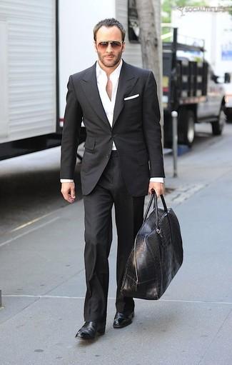 Cómo combinar: traje negro, camisa de vestir blanca, botines chelsea de cuero negros, bolso baúl de cuero negro