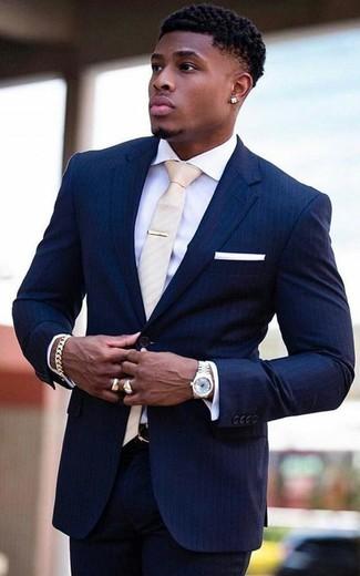 Cómo combinar: traje de rayas verticales azul marino, camisa de vestir blanca, corbata en beige, pañuelo de bolsillo blanco