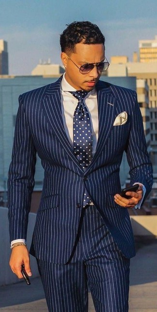 Cómo combinar: traje de rayas verticales en blanco y azul marino, camisa de vestir blanca, corbata a lunares en azul marino y blanco, pañuelo de bolsillo en beige
