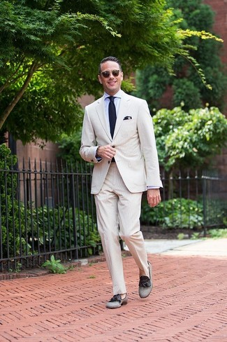 Cómo combinar: traje de seersucker en beige, camisa de vestir celeste, mocasín con borlas de lona gris, corbata de punto azul marino