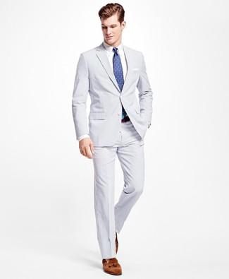 Cómo combinar: traje de seersucker blanco, camisa de vestir blanca, mocasín con borlas de ante marrón, corbata a lunares azul