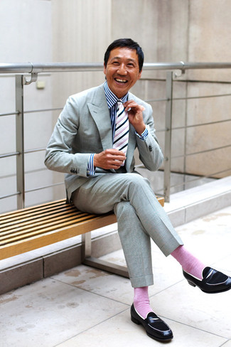 Cómo combinar: traje gris, camisa de vestir de rayas verticales en blanco y azul marino, mocasín de cuero negro, corbata de rayas verticales en blanco y negro