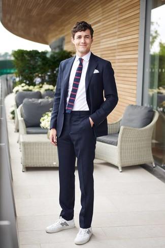 Cómo combinar: traje azul marino, camisa de vestir blanca, tenis de cuero blancos, corbata de rayas horizontales azul marino