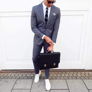 Cómo combinar: traje en gris oscuro, camisa de vestir blanca, tenis blancos, portafolio de cuero negro