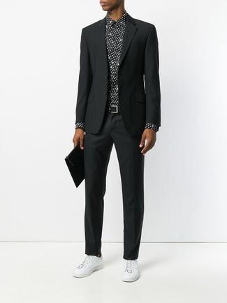 Cómo combinar: traje negro, camisa de vestir a lunares en negro y blanco, tenis de cuero blancos, bolso con cremallera de cuero negro