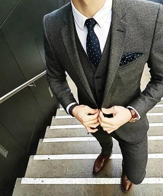 Cómo combinar: traje de lana gris, camisa de vestir blanca, zapatos brogue de cuero marrónes, corbata a lunares en negro y blanco