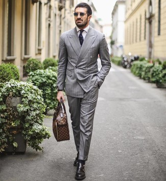 Cómo combinar: traje de rayas verticales gris, camisa de vestir blanca, zapatos con doble hebilla de cuero negros, portafolio de cuero marrón