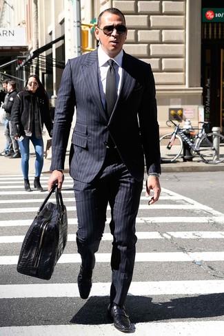 Cómo combinar: traje de rayas verticales azul marino, camisa de vestir blanca, zapatos con doble hebilla de cuero negros, bolsa de viaje de cuero negra