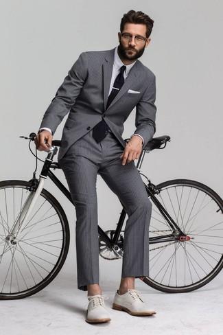 Cómo combinar: traje de rayas verticales gris, camisa de vestir blanca, zapatos derby de ante blancos, corbata negra