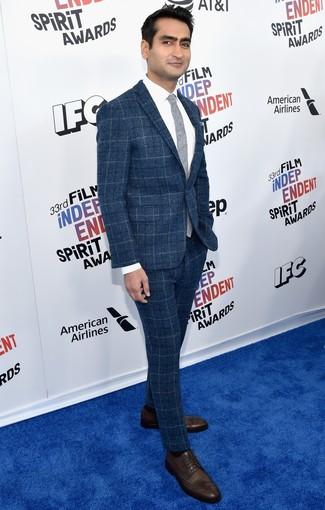 Cómo combinar: traje de lana a cuadros azul, camisa de vestir blanca, zapatos derby de cuero en marrón oscuro, corbata gris