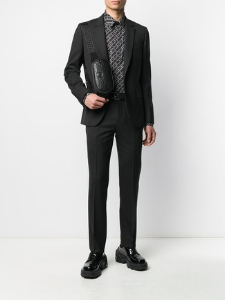 Cómo combinar: traje negro, camisa de vestir estampada en negro y blanco, zapatos derby de cuero gruesos negros, riñonera de cuero negra