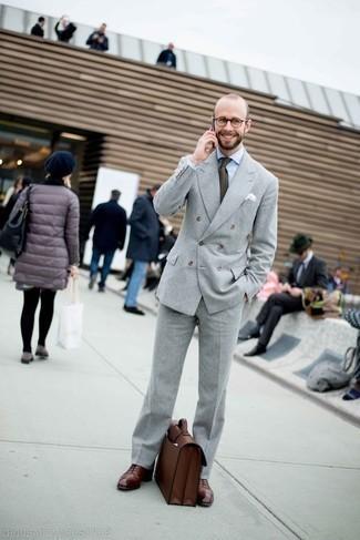 Outfits hombres: Opta por un traje gris y una camisa de vestir blanca para un perfil clásico y refinado. Este atuendo se complementa perfectamente con zapatos oxford de cuero burdeos.
