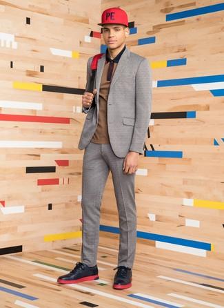 Cómo combinar: traje de lana gris, camisa polo marrón, tenis de cuero negros, mochila de lona roja