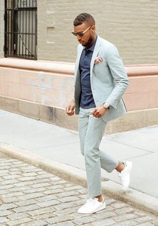 Cómo combinar: traje gris, camisa polo azul marino, tenis de cuero blancos, pañuelo de bolsillo estampado naranja